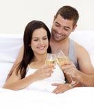 Amantes que bebem o champanhe na cama Fotos de Stock Royalty Free