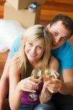 Amantes que celebran la nueva casa con champán Imagen de archivo