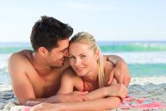 Amantes que encontram-se para baixo na praia Fotografia de Stock Royalty Free