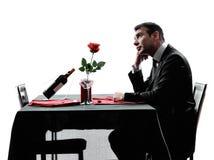 Amantes que esperam silhuetas do jantar Foto de Stock