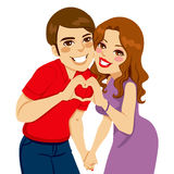 Amantes que fazem o sinal do amor do coração Imagem de Stock