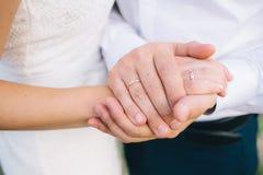 Amantes que guardam as mãos com alianças de casamento do ouro Fotografia de Stock Royalty Free