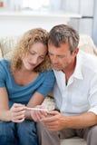 Amantes que miran una prueba de embarazo Imagen de archivo