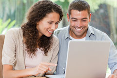 Amantes que olham seu portátil em casa Imagens de Stock