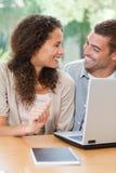 Amantes que olham seu portátil em casa Fotos de Stock Royalty Free
