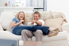 Amantes que prestam atenção à tevê na sala de visitas Foto de Stock Royalty Free