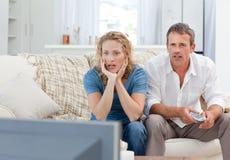 Amantes que prestam atenção à tevê na sala de visitas em casa Foto de Stock Royalty Free