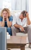 Amantes que prestam atenção à tevê na sala de visitas em casa Fotografia de Stock Royalty Free