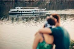 Amantes que se sientan en el banco del río contra el fondo de la nave Fotos de archivo