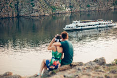 Amantes que se sientan en el banco del río contra el fondo de la nave Imagen de archivo libre de regalías