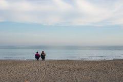 Amantes que se sientan en la costa Fotos de archivo libres de regalías