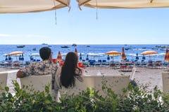 Amantes que se sientan, mirando en el cielo y el mar, mountion, debajo del paraguas de sol Vacaciones, turismo, hooneymoon Muchac fotografía de archivo libre de regalías
