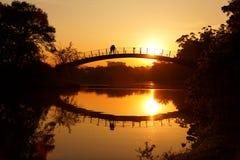 Amantes románticos de la puesta del sol en el puente Foto de archivo