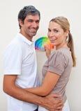 Amantes sonrientes con las muestras del color a pintar Foto de archivo libre de regalías