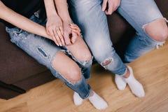 Amantes tímidos que se sientan junto en cama marrón Foto de archivo libre de regalías