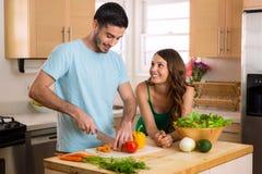 Amanti adatti dei giovani che producono alimento salutare affinchè pranzo e cena tengano nella forma Fotografie Stock Libere da Diritti