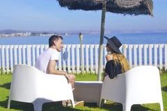 Amanti che collocano esaminando cielo ed oceano, mountion, sotto l'ombrello di sole Vacanza, turismo, luna di miele Ragazza con i Fotografia Stock