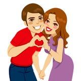 Amanti che fanno il segno di amore del cuore Immagine Stock