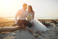 Amanti di Photoshoot in un vestito da sposa sulla spiaggia vicino al mare Fotografia Stock Libera da Diritti