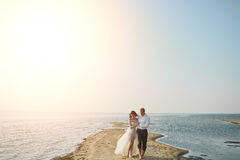 Amanti di Photoshoot in un vestito da sposa sulla spiaggia vicino al mare fotografie stock
