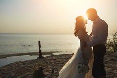Amanti di Photoshoot in un vestito da sposa sulla spiaggia vicino al mare Immagine Stock Libera da Diritti