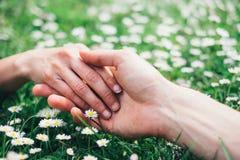 Amanti romantici che toccano le mani sui fiori della molla fotografia stock libera da diritti