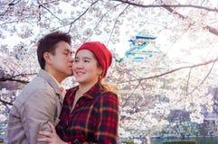 Amants asiatiques romantiques embrassant dans la saison de fleurs de cerisier Image stock