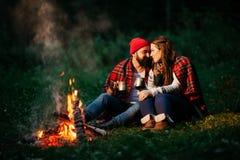 Amants autour du feu de camp la nuit Images stock