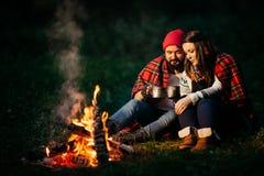 Amants autour du feu de camp la nuit Image stock