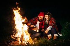 Amants autour du feu de camp la nuit Photographie stock