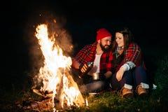 Amants autour du feu de camp la nuit Photos libres de droits