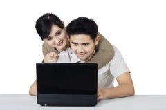 Amants avec l'ordinateur portable d'isolement au-dessus du blanc Image libre de droits