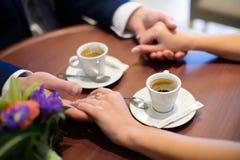 Amants buvant du café hors des tasses dans le café Photos libres de droits