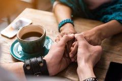 Amants collant des bras ensemble en café Photographie stock libre de droits