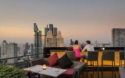 Amants dans une heure dinante crépusculaire à la terrasse d'un gratte-ciel découvert à Bangkok, Thaïlande photos stock