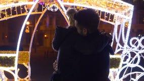 Amants embrassant et étreignant sur le marché du centre de Noël de la nuit banque de vidéos