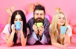 Amants en café de boissons d'amour dans le lit Le plan à trois détendent dans le matin avec du café Concept d'amants Homme et fem Photos stock