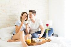 Amants faisant tinter des tasses de café sur le lit à la maison images stock