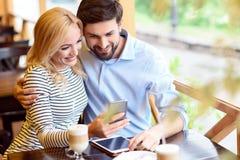 Amants gais détendant avec la technologie en café Photographie stock
