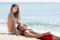 Amants heureux s'étendant sur la plage sablonneuse Photo stock