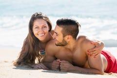 Amants heureux se reposant sur la plage sablonneuse Images stock