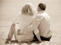 Amants mûrs s'asseyant sur la plage Photographie stock libre de droits