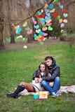 Amants marchant aux coeurs de papier de décor de parc au printemps Image stock