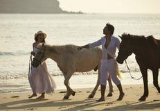Amants marchant sur la plage au coucher du soleil Images stock