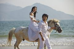 Amants marchant sur la plage avec le cheval Photo stock