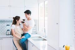 Amants ou couples asiatiques buvant du vin dans la chambre de cuisine à la maison L Photo libre de droits