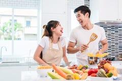 Amants ou couples asiatiques faisant cuire si drôle ensemble dans l'esprit de cuisine Image libre de droits