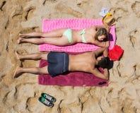 Amants se reposant sur le sable à la plage de mer Images stock