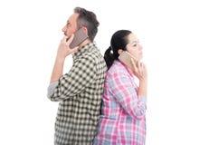 Amants se tenant de nouveau à parler arrière sur des téléphones portables Photo libre de droits