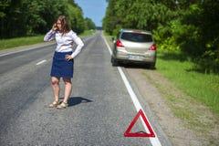 Łamany samochód na kobiecie z telefonem i poboczu Fotografia Stock